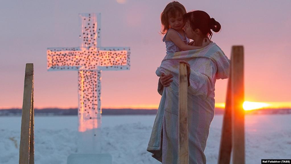 Ребенок плачет на руках у матери после погружения в ледяные воды озера Смолино в Челябинске. 19 января 2019 года