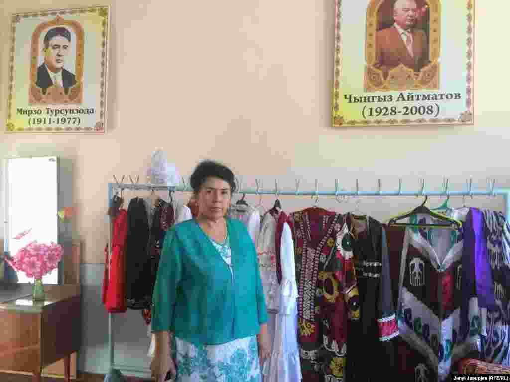 Директор школы им. Айни Абдураззакова Кумрихон у вешалки с национальными костюмами школьного ансамбля.