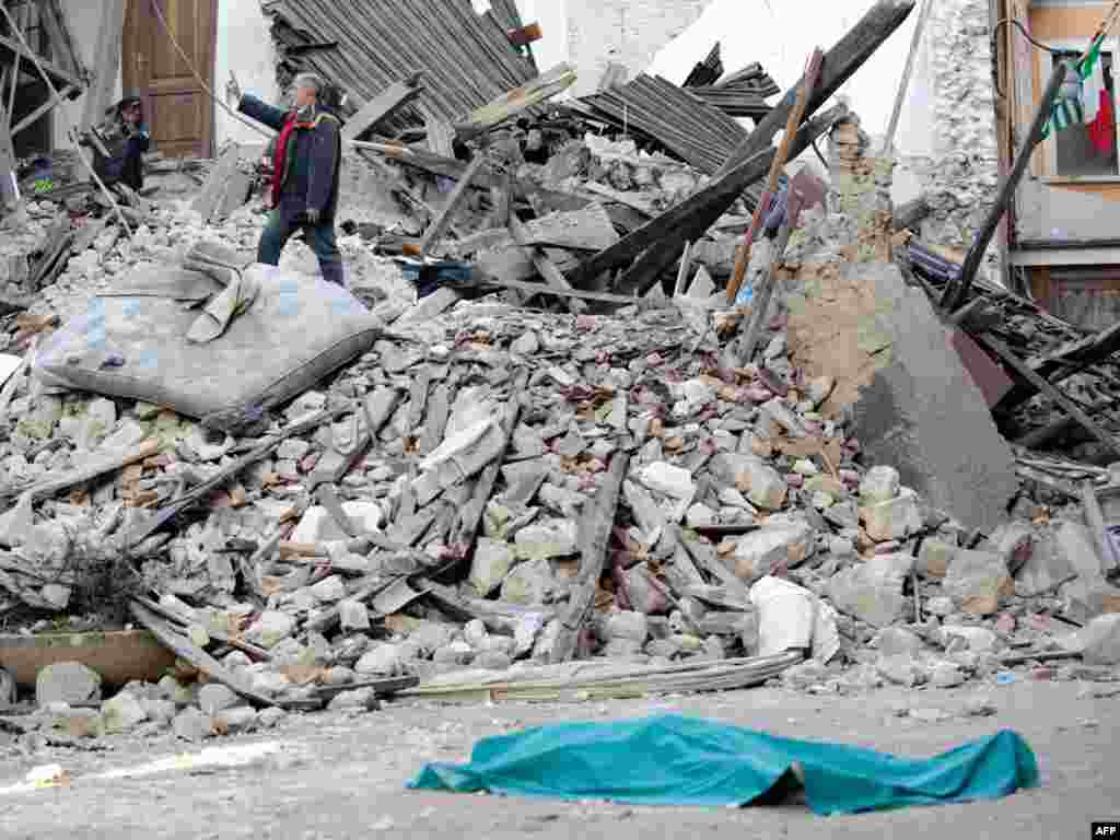 Italy - The body of a victim lies on the street in front of his collapsed house in the center of the Abruzzo capital L'Aquila, 06Apr2006 - Par2494641 Object name ITALY - EARTHQUAKE ITALY, L'Aquila : The body of a victim lies on the street on April 6, 2009 in front of his collapsed house in the center of the Abruzzo capital L'Aquila, the epicenter of an earthquake measuring 5.8-magnitude on the open-ended Richter scale. At least 20 people were killed in an earthquake that struck central Italy as most people lay sleeping early on April 6, and the death toll was rising steadily after many homes collapsed in the Abruzzo region. AFP PHOTO / VINCENZO PINTO