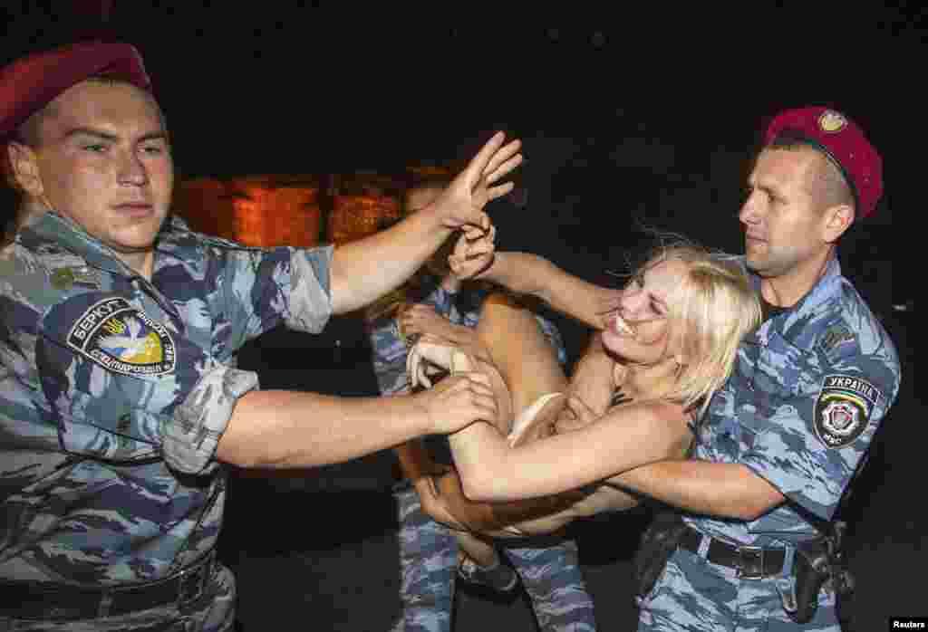 Беларусь президенті Александр Лукашенконың Украина астанасына сапары кезінде оған наразылық акциясына шыққан Femen белсендісін полицияның ұстаған сәті. Киев, маусым, 2013 жыл.