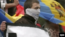 "Moldovan students hold a sign saying ""Europe Help Us"" protest in front of the government building in Chisinau on April 10."