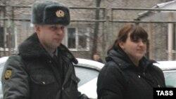 Гражданская активистка Таисия Осипова, которую обвинили в хранении наркотиков, идет в суд в сопровождении полицейского. Смоленск, 29 декабря 2011 года.