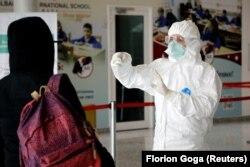 Një punonjës mjekësor kontrollon një pasagjere shqiptare që ka arritur në Shqipëri përmes Aeroportit të Tiranës.