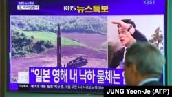 Мужчина у телеэкрана с новостным сюжетом о запуске Северной Кореей ракеты.