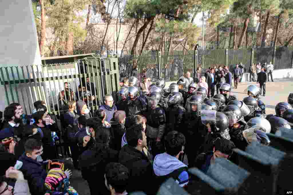 Iranian students scuffle with police at the University of Tehran during a demonstration driven by anger over economic problems on December 30. (AFP/Stringer)