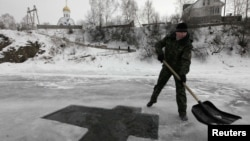 A worker prepares a cross-shaped bathing hole for Russian Orthodox Epiphany celebrations on the Mana River near the village of Ust-Mana on January 18.