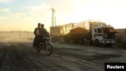 Чоловіки на мотоциклі минають знищену авіаударом вантажівку поблизу Алеппо, 20 вересня 2016 року