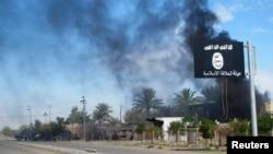 """Дым над флагом боевиков организации """"Исламское государство"""". 24 ноября 2014 года."""