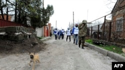 Monitors of the OSCE Special Monitoring Mission to Ukraine on a road in the village of Shyrokyne, on the outskirts of the strategic port city of Mariupol, on April 14.