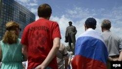 Люди стоят напротив памятника Ленину во время акции протеста против выборов президента Украины. Донецк, 25 мая 2014 года.