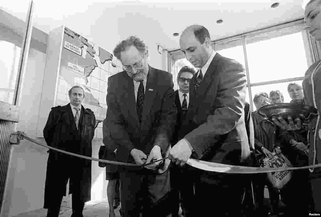Putin (left), chairman of St. Petersburg's External Relations Committee, takes part in a ceremony to open an electronics store in St. Petersburg on April 29, 1993.