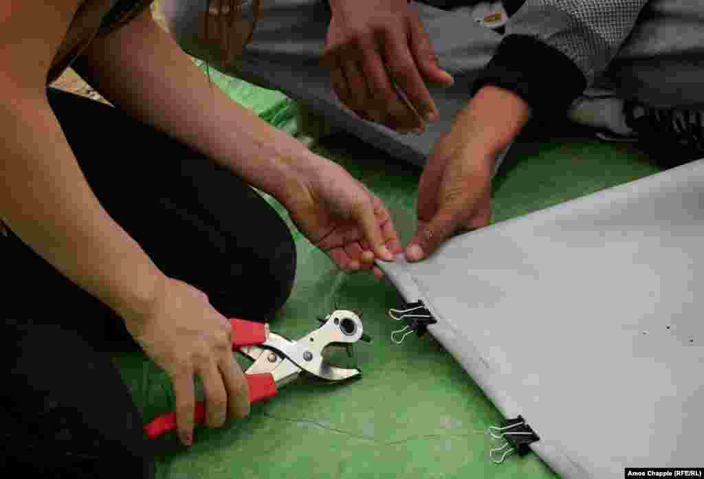 First, a volunteer demonstrates how to bind the material using a rivet gun. It was the first time using such a tool for many young migrants.