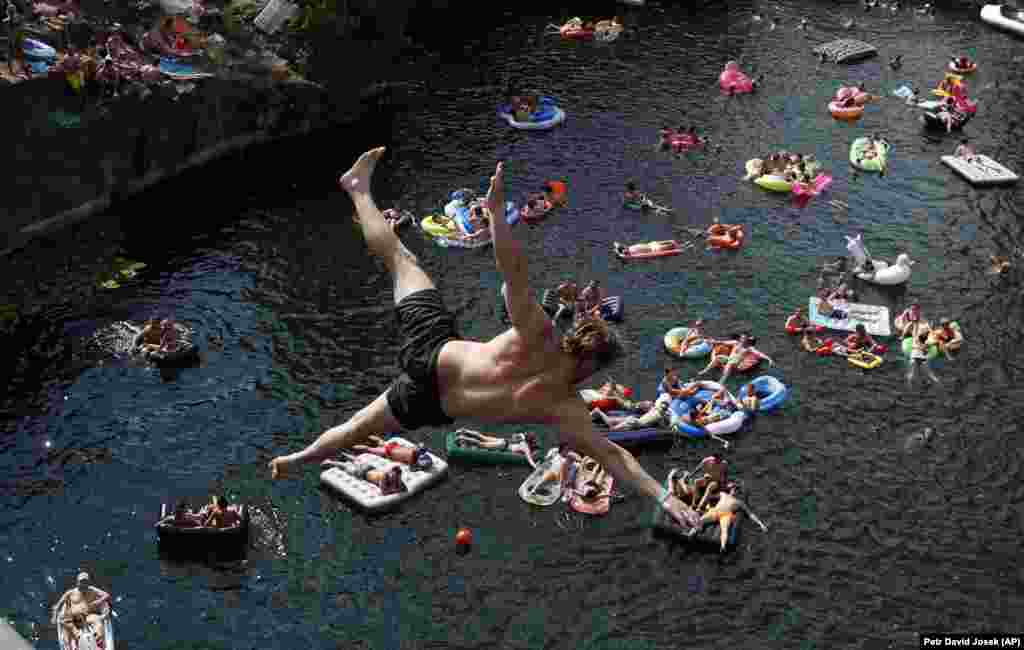 Spectators on inflatable mattresses watch as a competitor jumps into the water during a cliff-diving competition at a flooded quarry near the village of Hrimezdice in the Czech Republic on August 3. (AP/David Josek)