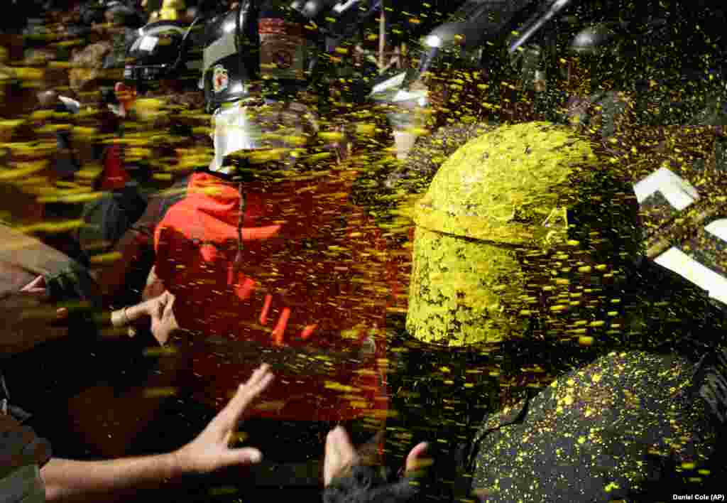 Pro-independence demonstrators throw paint at Catalan police officers during clashes in Barcelona. Catalan separatists clashed with police as tensions increase before the anniversary of the Spanish region's illegal referendum on secession that ended in violent raids by security forces. (AP/Daniel Cole)