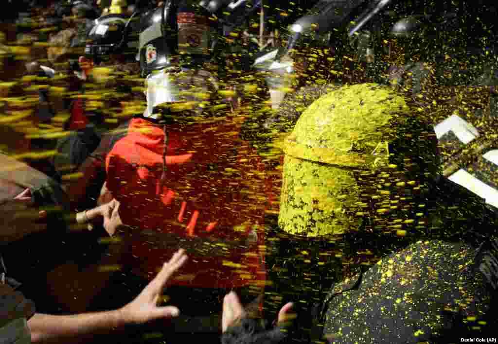 Прыхільнікі незалежнасьці Каталёніі абкідваюць паліцыю фарбамі падчас дэманстрацыі ў Барсэлёне 29 верасьня.