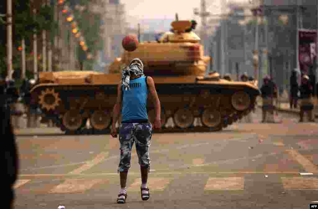 An opposition supporter plays football next to a Republican Guard tank deployed outside the presidential palace in Cairo. Egypt's 51 million voters are being called on to vote over the next two weekends in a referendum on a draft constitution backed by Islamists, including President Muhammad Morsi, but denounced by the secular opposition. (AFP/Patrick Baz)