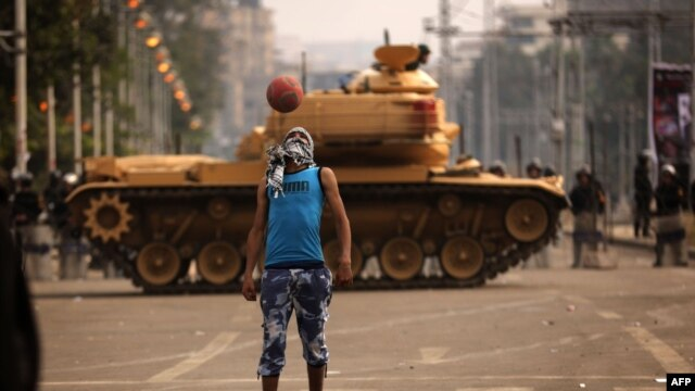 An opposition supporter plays football next to a Republican Guard tank deployed outside the presidential palace in Cairo.