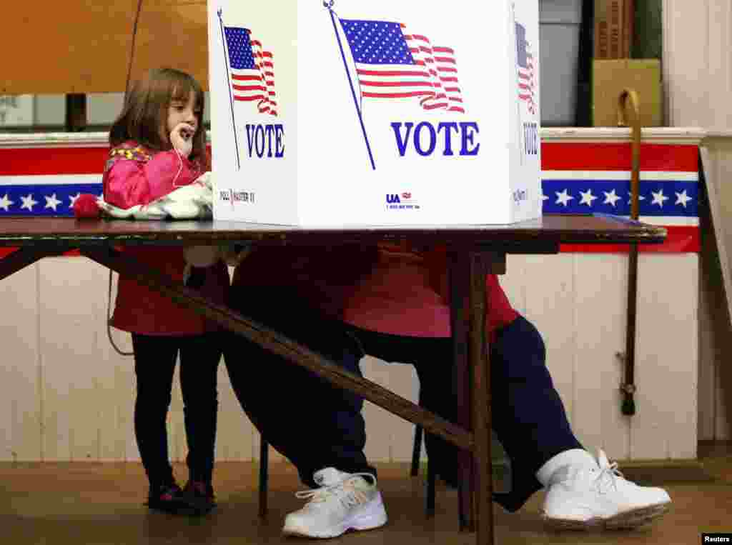 A girl watches as her grandmother votes at the old Town Hall in Bristol, New Hampshire.