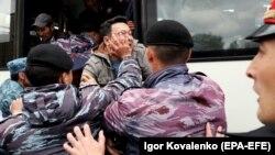 Полицейские заталкивают в автобус участника антиправительственного протеста в Нур-Султане. 9 июня 2019 года.