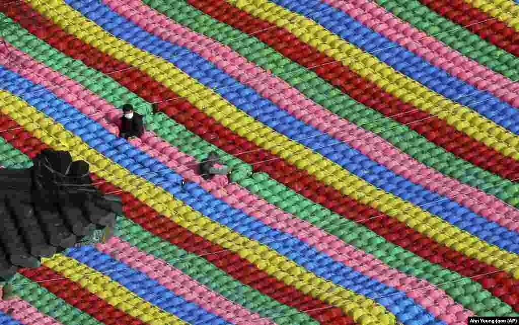 Рабочыя ставяць асьвятленьне для будучага сьвяткаваньня дня нараджэньня Буды 22 траўня ў храме ў Сэуле, Паўднёвая Карэя. (AP/Ahn Young-joon)