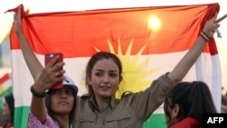 A woman holds a flag during a gathering to support the Kurdistan independence referendum on September 21.