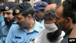 Pakistani policemen escort Islamic cleric Khalid Chishti upon his arrival at a court in Islamabad on September 2.