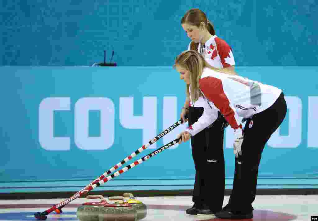 Canada's Jennifer Jones (bending over) and Kaitlyn Lawes ponder their options during the semifinal match between Great Britain and Canada in the women's curling competition. (EPA/Tatyana Zenkovich)
