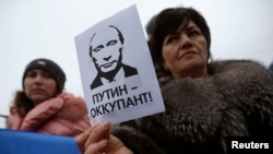 "Ukraine -- A woman holds a sign with a portrait of Russian President Vladimir Putin and the words ""Putin - Occupant"" during a pro-Ukrainian rally in Simferopol, March 11, 2014"