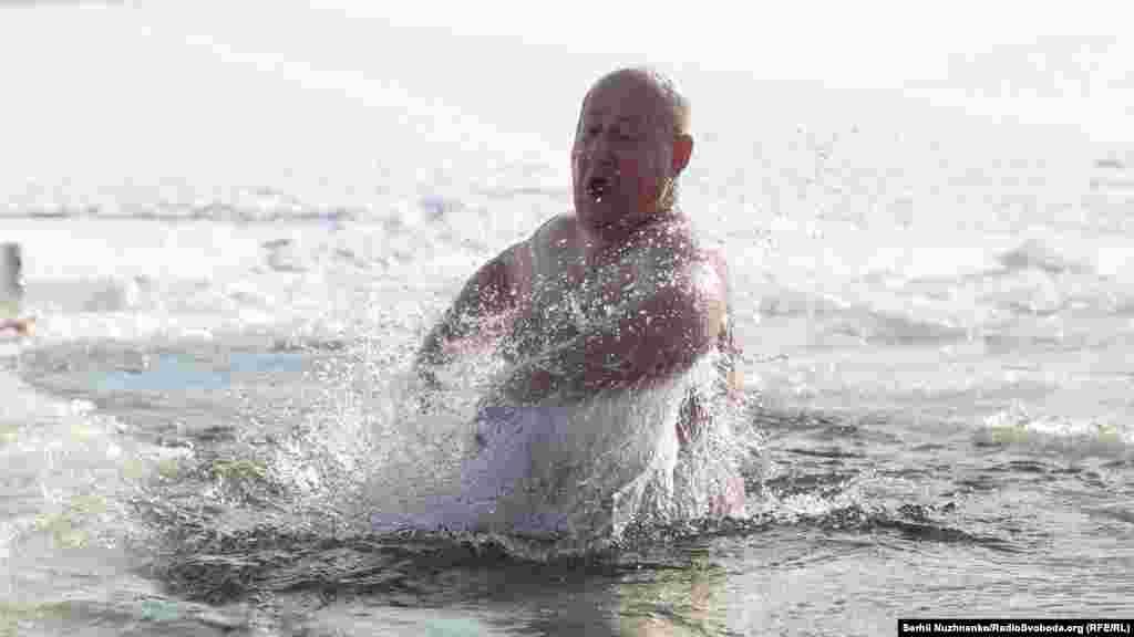 Чоловік виринає з крижаної води на Водохреще. Київ