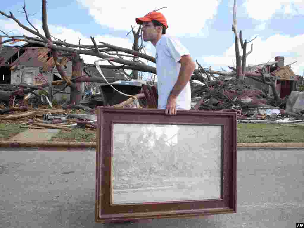 In the aftermath of a severe tornado, Dennis Hinton removes belongings from his destroyed home in the Cedar Crest neighborhood of Tuscaloosa, Alabama. Photo by Jessica McGowan for Getty Images.