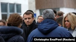 France, Paris, French President Emmanuel Macron, and his wife Brigitte speak to relatives of victims outside the satirical newspaper Charlie Hebdo former office