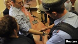 A policeman puts handcuffs on opposition leader Aleksei Navalny (left) in a courtroom in Kirov on July 18. The next day, Navalny was freed as appeals of his five-year sentence are heard.