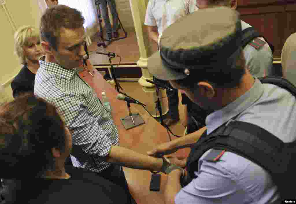 A policeman puts handcuffs on protest leader Aleksei Navalny inside the courtroom in Kirov.