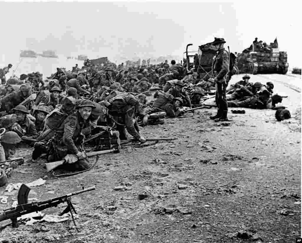 After landing at the shore, these British troops wait for the signal to move forward, during the initial Allied landing operations in Normandy, France, June 6, 1944