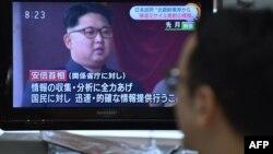 یک شهروند ژاپنی در حال تماشای اخبار مربوط به آزمایش موسودان در توکیو است؛ بر صفحه تلویزیون تصویری از کیم جونگاون دیده میشود