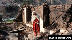 A Kashmiri woman stands amid the debris of her home that was reportedly destroyed by cross-border shelling from Indian troops, in the Neelum Valley, situated at the de facto border in Pakistani Kashmir on December 23.