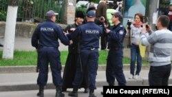 Молдовалық ЛГБТ белсендісін ұстап жатқан полиция. Көрнекі сурет.