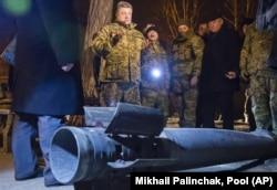 Dressed in military fatigues, Ukrainian President Petro Poroshenko talks to reporters beside an unexploded rocket in Kramatorsk in February 2015.