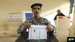 An Iraqi officer casts his vote in central Baghdad