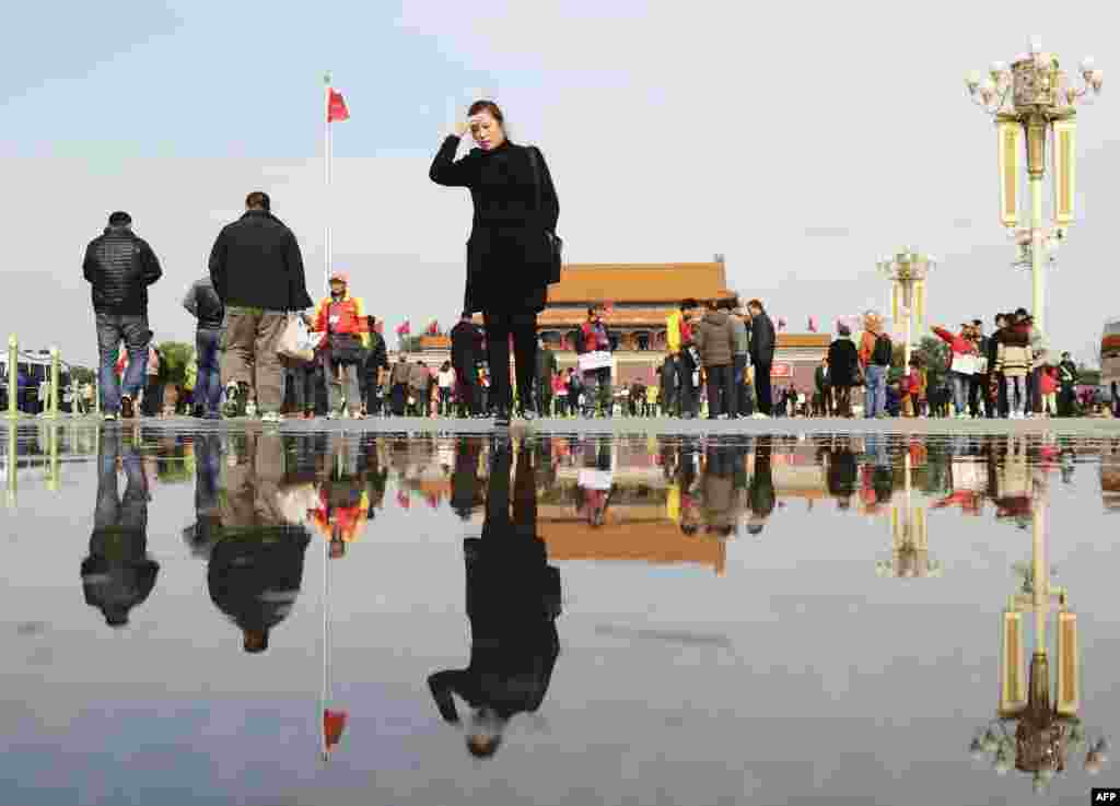 People stroll through Tiananmen Square in Beijing.