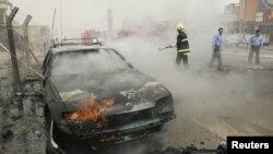 رجل إطفاء يحاول إخماد حريق في سيارة تحترق إثر إنفجار في كركوك