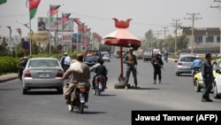Afghan police guard at a checkpoint in Kandahar Province, site of a deadly attack on October 18.
