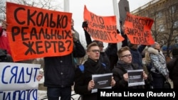"People hold placards during a demonstration in Kemerovo on March 27. The signs say: ""How many real victims?""; ""Who is really to blame?""; ""How much do your closed eyes cost?""; and ""Corruption kills."""