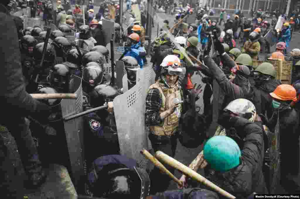 Доброволец пытается разъединить милицию и демонстрантов.