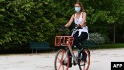 زنی ماسک بر چهره در میلان ایتالیا سوار بر دوچرخه کرایهای