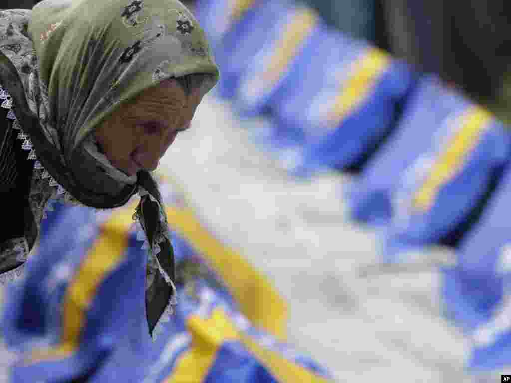 A Bosnian Muslim woman searches for the coffin of her relative among coffins displayed during a mass funeral for Bosnian Muslims in Bratunac, Bosnia-Herzegovina, on May 12. Thousands of Bosnian Muslims attended the funeral of 16 men, women, and children killed by Bosnian Serb forces at the beginning of the 1992-95 war and exhumed from a mass grave.Photo by Amel Emric for AP