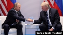 U.S. President Donald Trump (right) shakes hands with Russia's President Vladimir Putin in Hamburg, Germany, in July, the only face-to-face meeting between the two, so far.