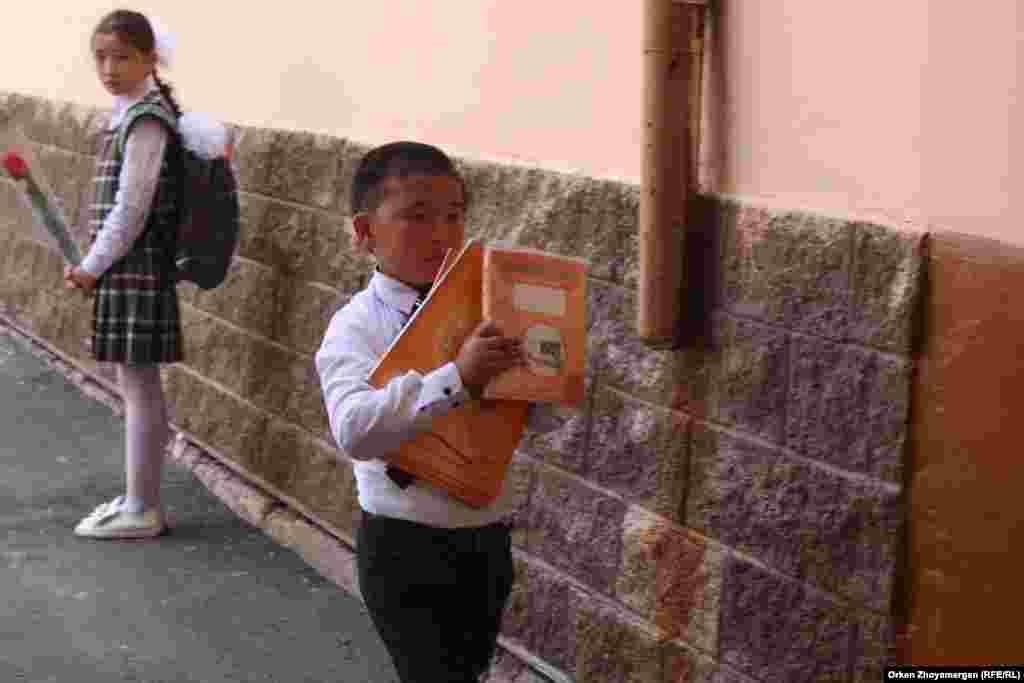 Мектептен жаңа оқу жылына арналған оқулықтар алған шәкірттер.