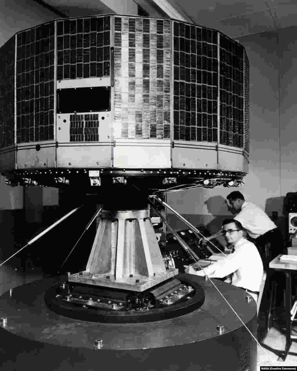 NASA's Tiros 1 weather satellite being jiggled during a test to see if it will survive the violent ride into space in 1960. Tiros was the first attempt at a weather satellite that could transmit a view of incoming weather from its two cameras to a control center back on Earth.