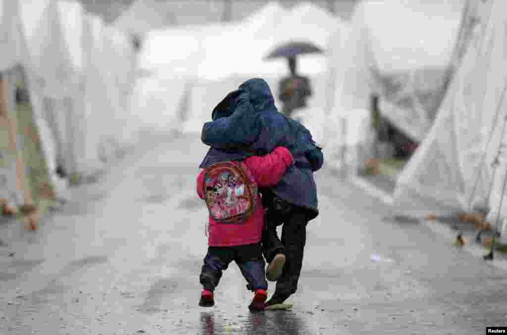 Syrian boys walk shoulder-to-shoulder in the rain at the Boynuyogun refugee camp on the Turkish-Syrian border.
